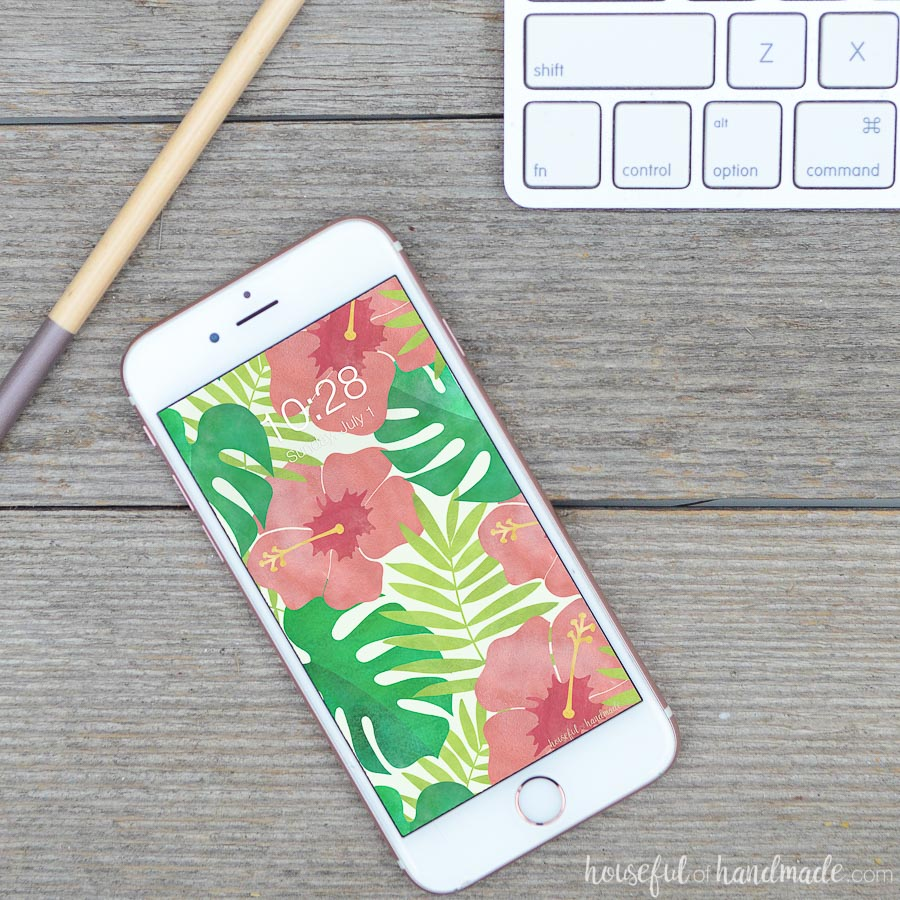 iPhone with hibiscus water color digital background on wooden desk with pencil and keyboard.