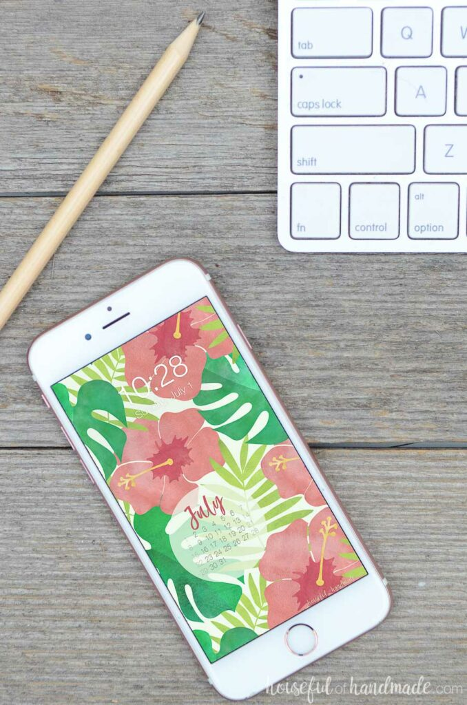 cell phone at an angle on a wood desk displaying watercolor digital background with a calendar.