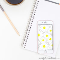 White smartphone with daisy print digital wallpaper on the screen.