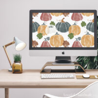 iMac computer on a desk with the free digital backgrounds for October on the screen. New October 2018 calendar on the background.