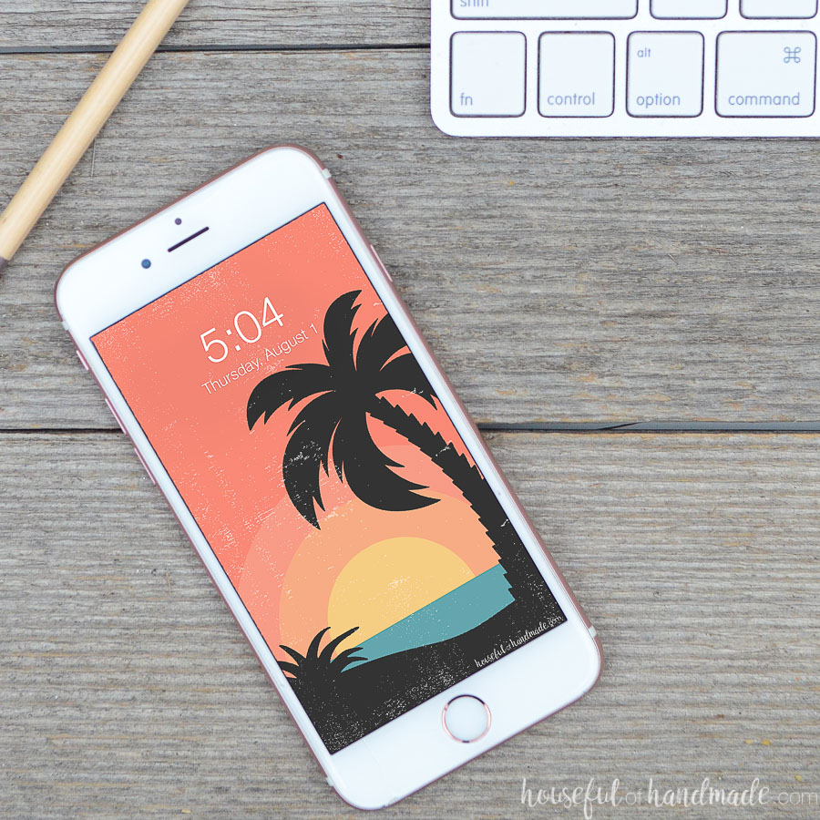 Rose gold iPhone with a retro tropical sunset digital wallpaper on the home screen.