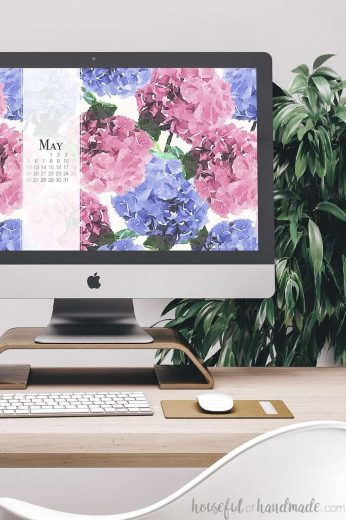 Computer with free digital backgrounds for May on the screen with May 2019 calendar.