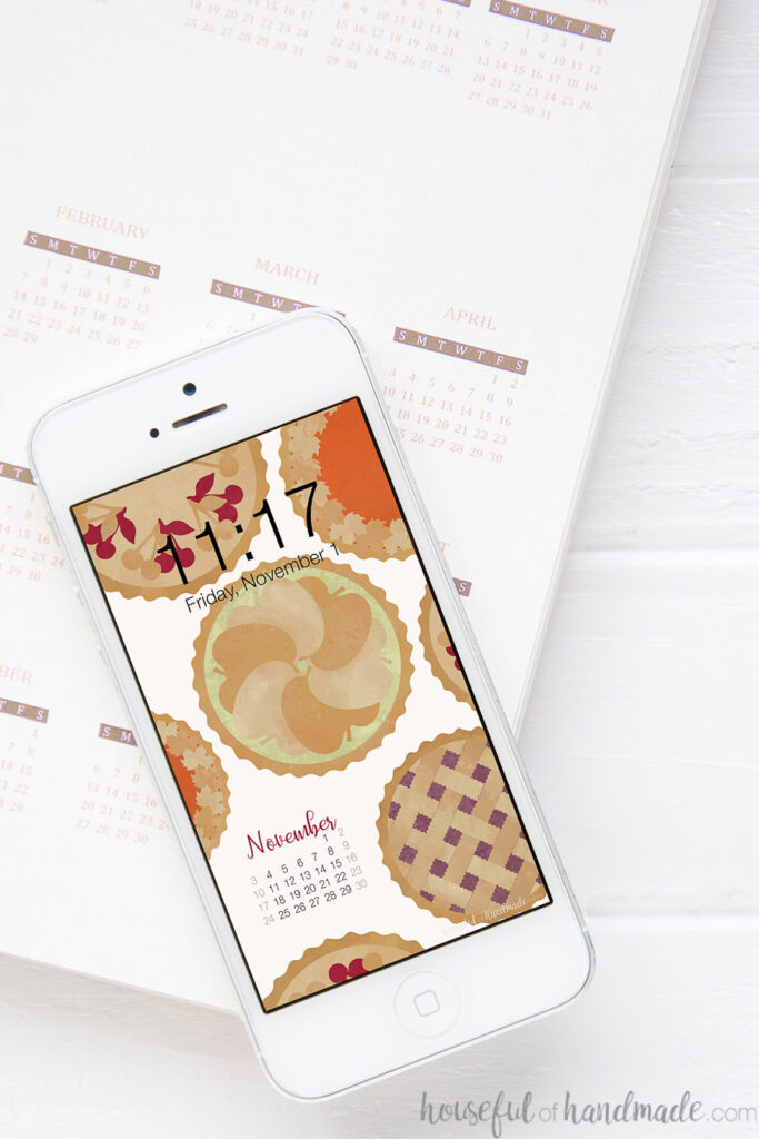 Smartphone laying on top of a planner with a pie print on the screen as digital wallpaper.