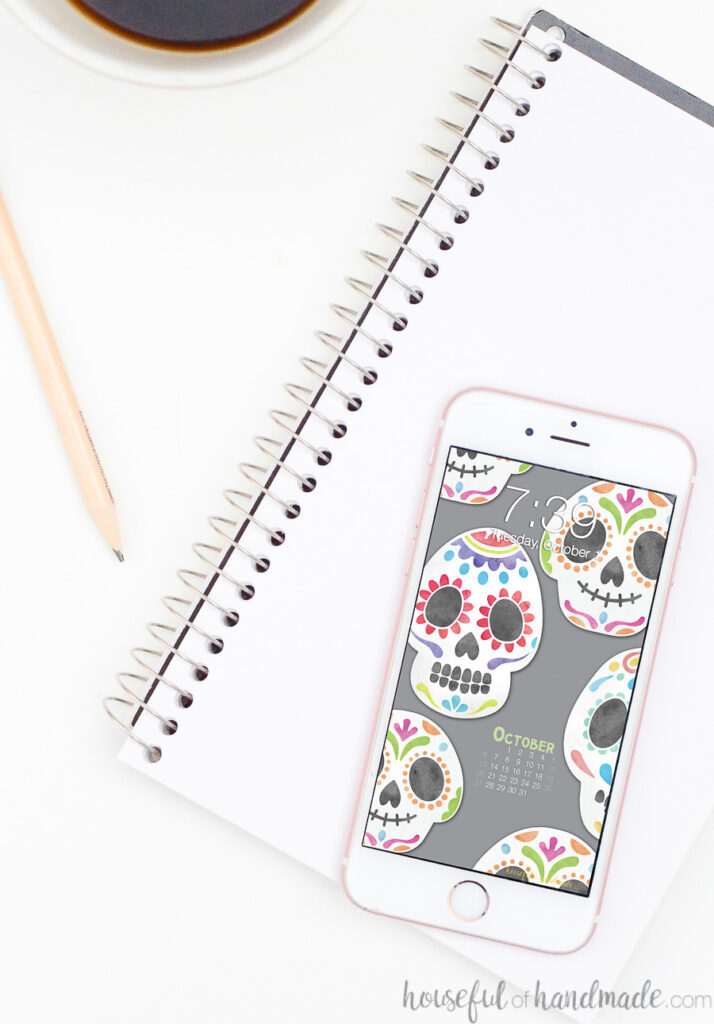 White iPhone with watercolor sugar skull designed wallpaper on the screen.