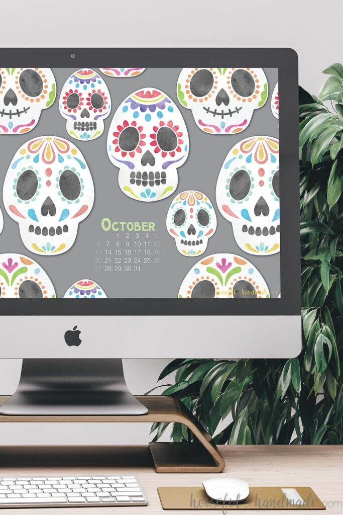 iMac computer on a desk with sugar skull digital wallpaper for October on the screen.