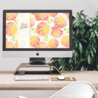 Desktop computer with watercolor dahlia wallpaper on the screen.