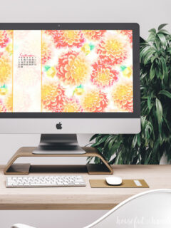 Desktop computer with watercolor dahlia wallpaper on the screen.