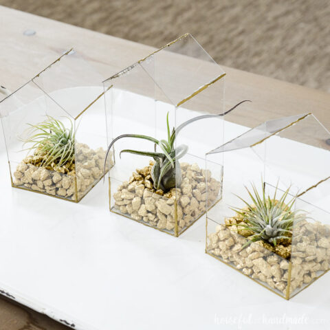 Three small house shaped air plant holders made from clear plastic sheets filled with gold rocks and air plants.