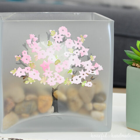 Large glass candle holder decorated with a frosted tree and spring blossoms on a tray in a living room.