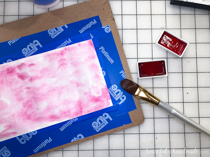 watercolor paper and paints on table with paint brush