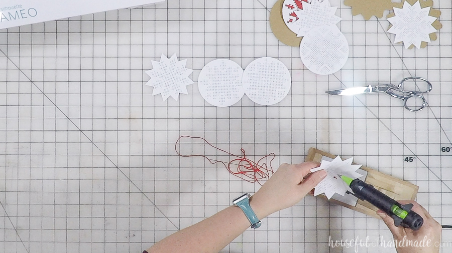 hot glue gun being used on nordic cross stitch ornaments
