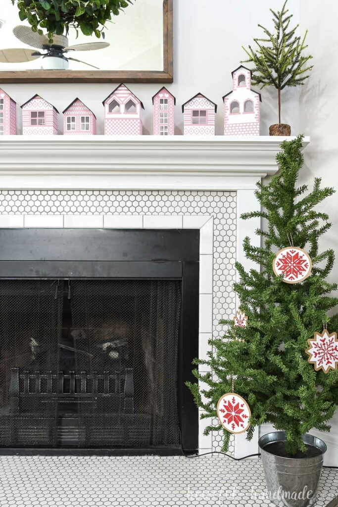 Christmas tree decorated with nordic cross tree ornaments next to fireplace