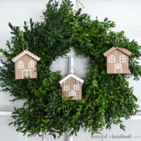 Three paper Christmas ornaments that look like gingerbread houses hanging in a wreath.