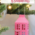 Soft pink paper lantern Christmas ornament hanging on a Christmas tree with words on it.