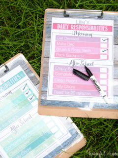 Printable Daily Chore Charts on clip boards on the grass
