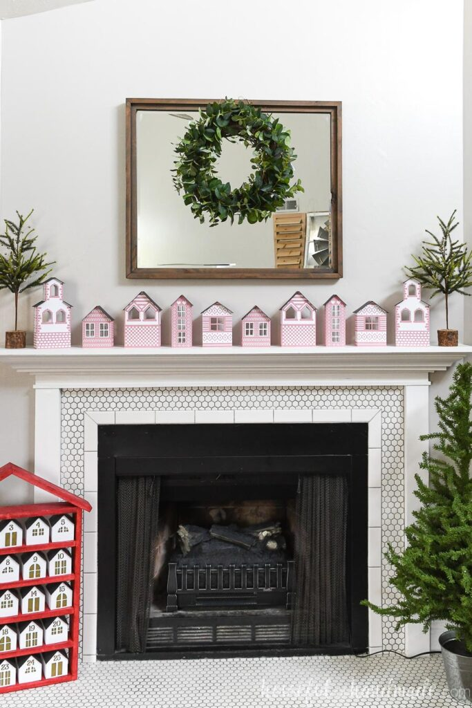 scandanavian christmas village paper houses on mantel with mirror and wreath