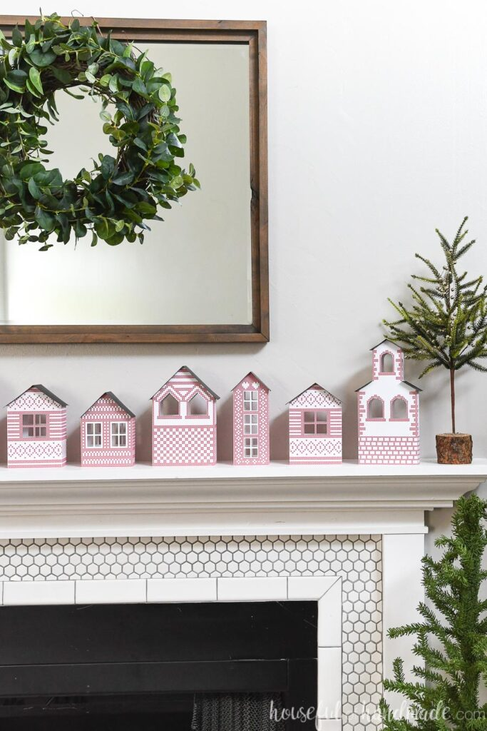paper Christmas village on mantel with wreath above on mirror