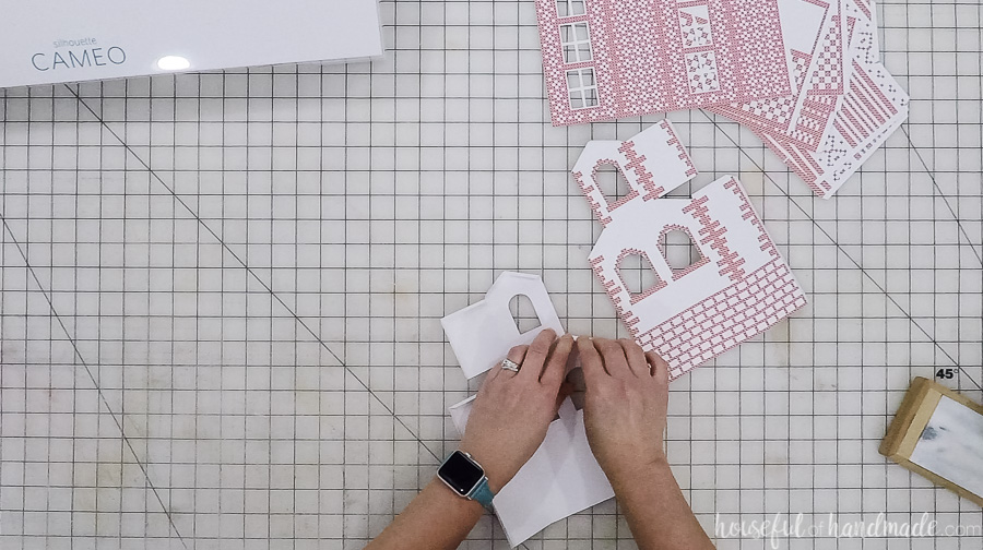 Scandinavian Paper Christmas Village cut outs in process of folding