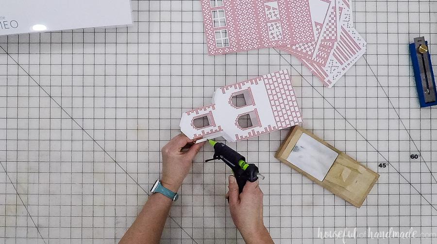 assembling paper christmas village houses with glue gun
