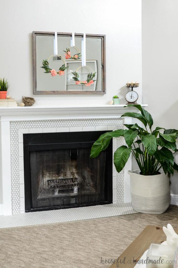 fireplace mantel decorated for spring with hoop wreaths