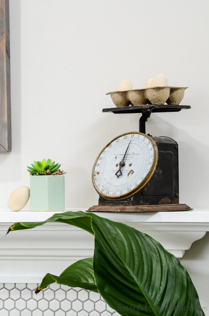 vintage scale with egg holder on top of spring mantel