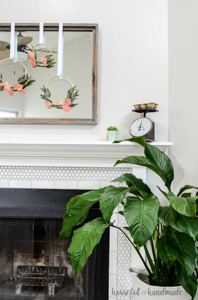3 hoop wreaths on mirror above spring mantel with plant