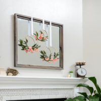 Gray mirror over fireplace with simple spring mantel decor on and around it.