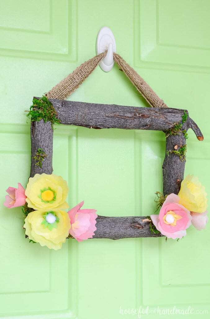 spring wreath with tree branches on green door