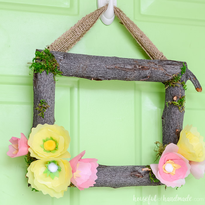 Square wreath made out of branches and tissue paper flowers to make a spring wreath.