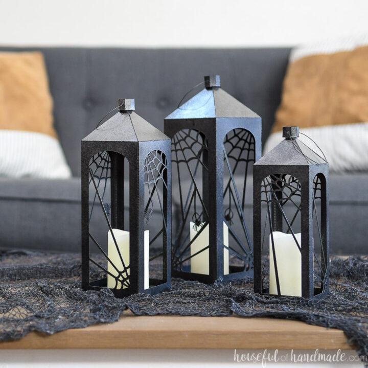 Three paper Halloween lanterns on a table with black creepy cloth.