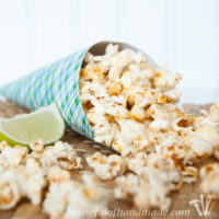 Cone of blue and green plaid paper full of chipotle lime popcorn with a lime wedge on the side.