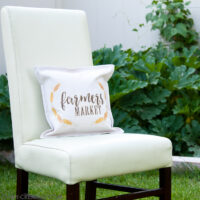 Chair sitting in the yard with decorative pillow made from a printable on the front.