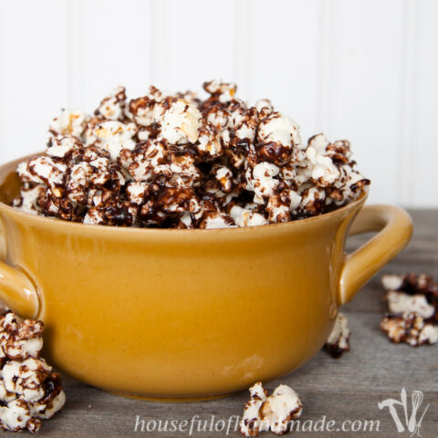Yellow dish full of dark chocolate caramel popcorn with some spilling over the sides.