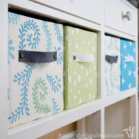 Four fabric storage boxes made from cardboard boxes on a shelf in a white console table.