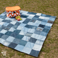 Picnic table made from recycled jeans sitting on the grass with an orange picnic basket on it.