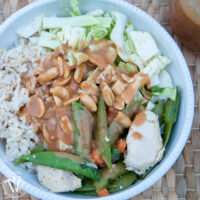 Bowl of brown rice with sautéed vegetables with peanut sauce on top.