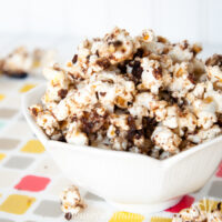 Tulip bowl on a colorful placemat filled with german chocolate cake caramel popcorn.