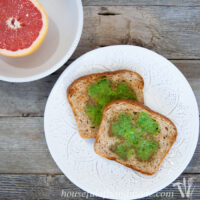 Two slices of wheat toast with green eggs in the shape of shamrocks cooked in the center.