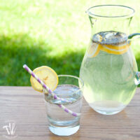 Glass pitcher full of lavender lemon water and cup next to it.