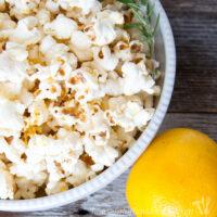 White bowl full of lemon rosemary flavored popcorn next to a lemon.