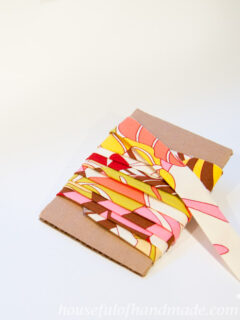 Cardboard scrap with homemade bias tape from printed fabric wrapped around it.