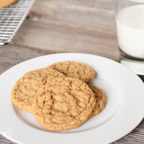 Four malted peanut butter oatmeal cookies on a white plate.