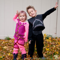 Young boy dressed in a DIY Sharkboy costume and little girl in a DIY lava girl costume outside in a pile of leaves.