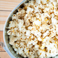 Silver bucket full of sharp cheddar cheese popcorn made with real cheese on wood surface.