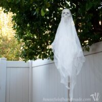 Outdoor Halloween decoration of a skull ghost craft hanging in a tree.