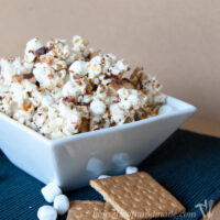 Square white bowl with s'mores caramel popcorn inside it.