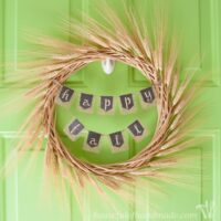DIY fall wreath made from wheat with a chalkboard banner hanging on a green door.