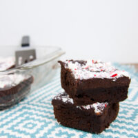 Two chewy chocolate brownies with peppermint ganache in a stack on a blue and white tablecloth.