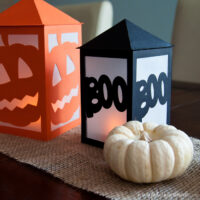 Black boo lantern next to white mini pumpkin with orange pumpkin lantern in the background.