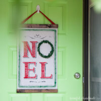 DIY Christmas scroll with Noel on it hanging on a front door as a wreath.